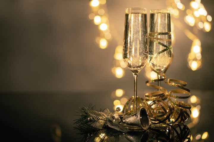 close up of two flute glasses filled with sparkling wine wuth ribbons and christmas decor